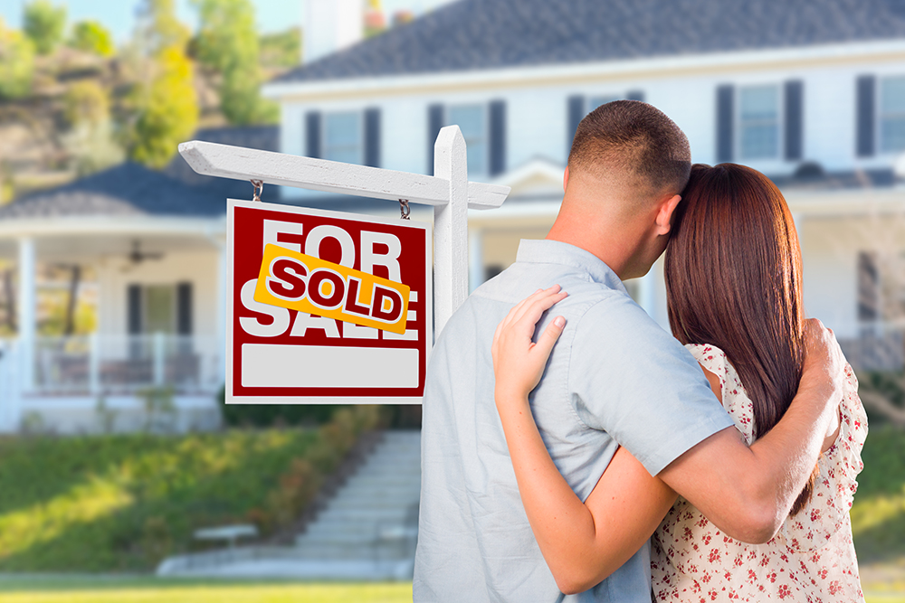 Couple Looking At House with Sold For Sale Real Estate Sign In Front.