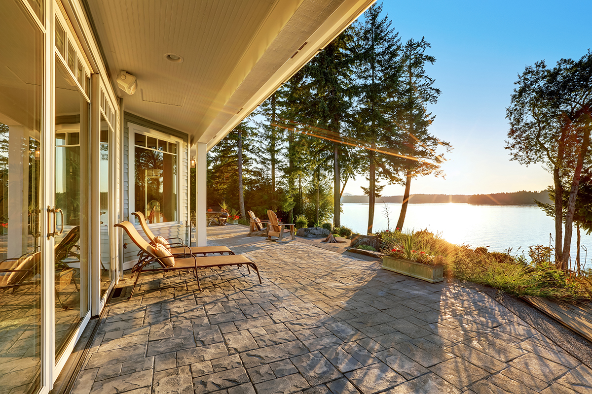 Large stone floor patio area of waterfront house with outdoor furniture, beautiful water view at sunset