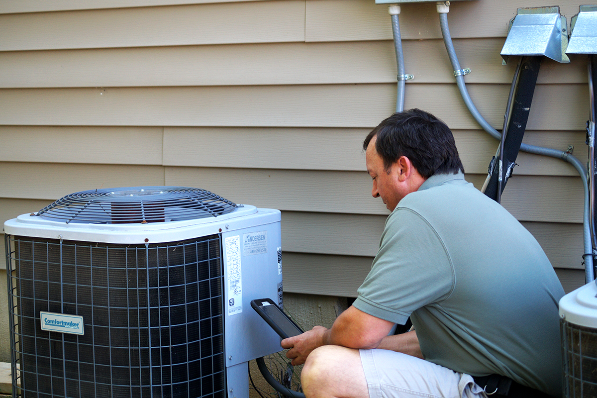 Home Inspector Mitch Wyatt inspecting an air conditioning unit.