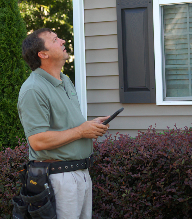 Home inspector Mitch Wyatt looking up at the exterior of a home